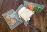 sandwich, celery and cookies, each in a food storage bag