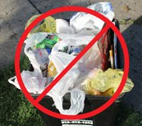 "Photo of recycling bin with plastic bags mixed with acceptable materials, with international ""no"" symbol (red circle with diagonal line through center) superimposed over image"